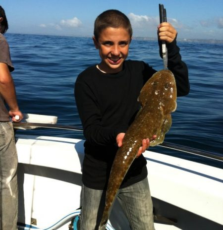 A boy smiling with a brown fish on Wahoo Fishing Charters boat.